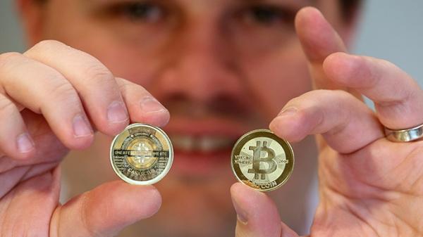 Ahli perangkat lunak, Mike Caldwell memperlihatkan bagian depan dan belakang sebuah Bitcoin fisik di tokonya yang berlokasi di Sandy, Utah. (AFP Photo / George Frey)